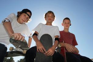 Three teenage boys with skateboardsの写真素材 [FYI03633578]