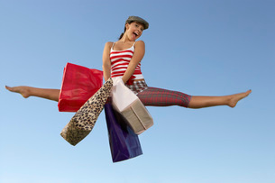 woman jumping with shopping bagsの写真素材 [FYI03633589]