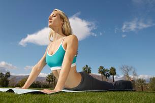 woman performing yoga exercises in parkの写真素材 [FYI03633595]