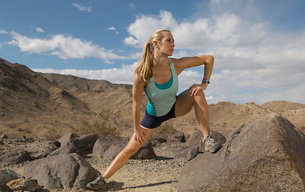 Female jogger stretching in mountainsの写真素材 [FYI03633604]