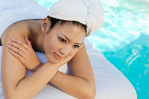 Chinese woman lying by swimming poolの写真素材 [FYI03633614]