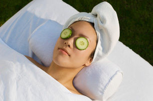 Young woman with cucumbers over eyesの写真素材 [FYI03633615]