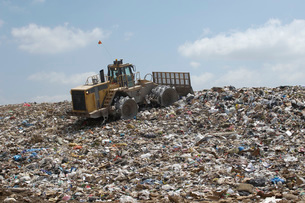 Digger working at landfill siteの写真素材 [FYI03633618]