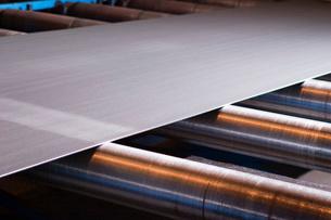 Sheet of metallic material being fed through machineの写真素材 [FYI03633638]