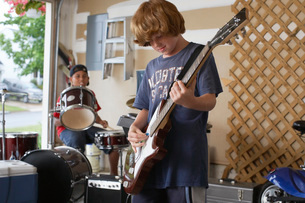 Two boys playing drums and guitar in garageの写真素材 [FYI03633641]