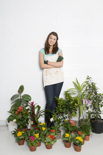 Portrait of woman surrounded by various potted plantsの写真素材 [FYI03633689]