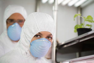 Workers in masks and suits in laboratoryの写真素材 [FYI03633703]