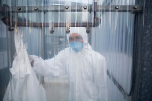 Worker in protective mask and suit behind plastic wallの写真素材 [FYI03633711]