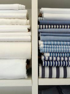 Two piles of cotton towels on shelfの写真素材 [FYI03633721]