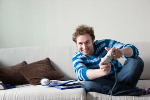 Man using computer game controls sitting on sofaの写真素材 [FYI03633737]