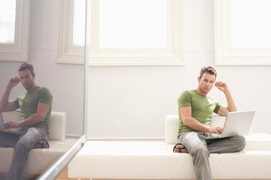 Young man with laptop on sofaの写真素材 [FYI03633750]