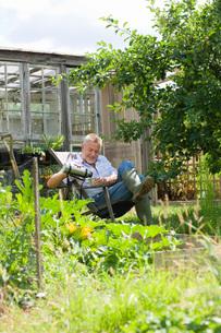 Senior man pouring drink, sitting in gardenの写真素材 [FYI03633795]