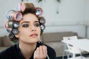 Model in Hair Curlers Applying Lip Glossの写真素材 [FYI03633843]