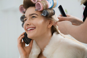 Model on Cell Phone While Having Hair Curledの写真素材 [FYI03633845]