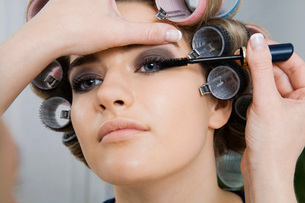 Model in Hair Curlers Having Makeup Appliedの写真素材 [FYI03633846]