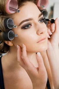 Model in Hair Curlers Having Makeup Appliedの写真素材 [FYI03633850]