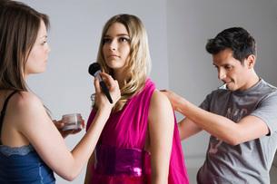Designer and Makeup Artist Preparing Model for Photo Shootの写真素材 [FYI03633855]