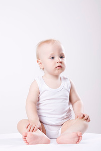 Baby boy sitting on floor, studio shotの写真素材 [FYI03633972]