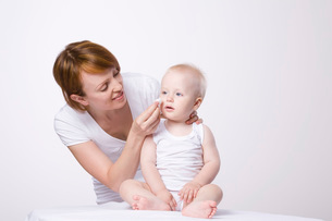 Woman cleaning baby's face, studio shotの写真素材 [FYI03633976]