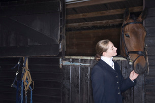 Female horseback rider with horse in stableの写真素材 [FYI03633987]