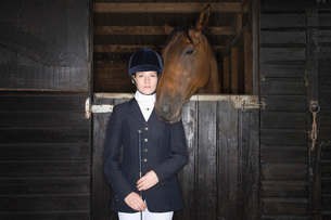 Portrait of Female horseback rider with horse in stableの写真素材 [FYI03633990]