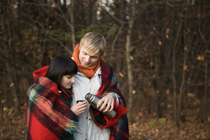 Young couple wrapped in blanket, embracing in forestの写真素材 [FYI03634097]