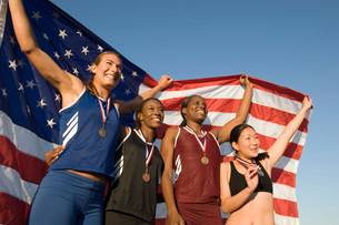 Four female athletes celebrating and holding american flagの写真素材 [FYI03634140]