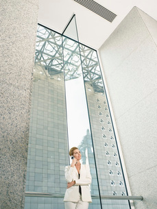 Businesswoman using mobile phone in office buildingの写真素材 [FYI03634148]
