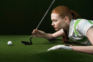 Woman reclining on floor holding golf club looking at a ballの写真素材 [FYI03634174]