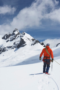 Hiker connected to safety line in snowy mountains back viewの写真素材 [FYI03634178]