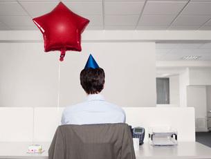 Man celebrating birthday working alone in officeの写真素材 [FYI03634189]