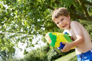 Boy in park shooting pump action water pistolの写真素材 [FYI03634248]