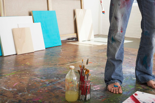 Artist standing by paint brushes and paint thinner in studioの写真素材 [FYI03634279]