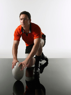 Rugby player kneeling on one knee holding ballの写真素材 [FYI03634346]