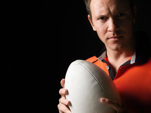 Rugby player holding ball close-up portraitの写真素材 [FYI03634348]