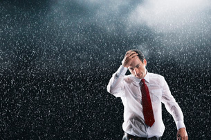 Businessman running hands through wet hair standing in Rainの写真素材 [FYI03634367]