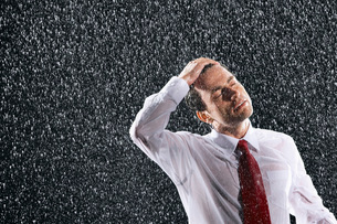 Businessman running hands through wet hair standing in Rainの写真素材 [FYI03634372]