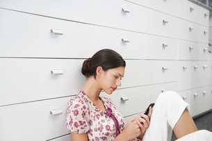 Young woman sitting by cabinet using mobile phone side viewの写真素材 [FYI03634503]