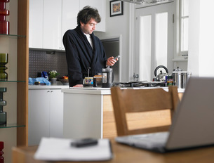 Man standing in kitchen text messaging laptop on tableの写真素材 [FYI03634525]