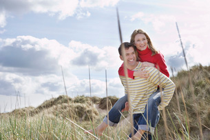 Man giving woman piggy back on dunesの写真素材 [FYI03634556]