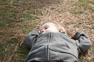 Boy taking a nap on grass high angle viewの写真素材 [FYI03634738]