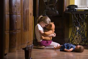 Girl embracing teddy bear on floor in homeの写真素材 [FYI03634896]