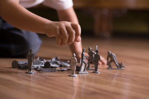Boy playing with toy soldiers on floorの写真素材 [FYI03634907]