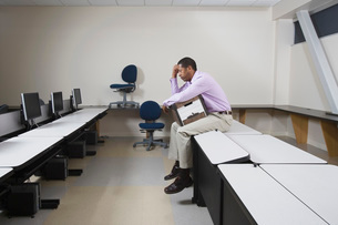 Depressed Man Sitting on Desk with Moving Boxの写真素材 [FYI03634944]