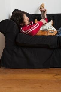 Young man lies on sofa playing electric guitarの写真素材 [FYI03634989]