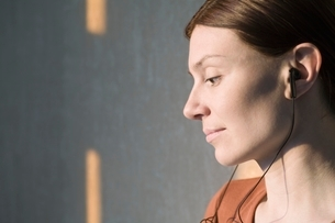 Side profile of redhead listening to headphonesの写真素材 [FYI03634993]