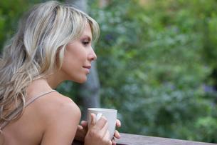 Blonde woman sits with cup on garden verandaの写真素材 [FYI03634999]