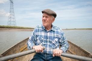 Elderly man rowing a boat on a reservoirの写真素材 [FYI03635004]