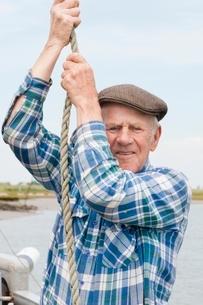 Elderly fisherman hauling ropeの写真素材 [FYI03635011]