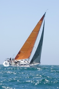 Yacht with yellow sail competes in team sailing eventの写真素材 [FYI03635039]